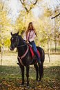 A girl sits riding on a black horse in an autumn park. Royalty Free Stock Photo