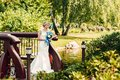 Beautiful young fair-haired bride stands on a bridge in an exotic park Royalty Free Stock Photo