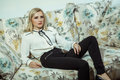 Beautiful young fashion caucasian blonde model posing on sofa. Royalty Free Stock Photo