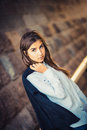 Beautiful young fashionable girl standing against the stone wall Royalty Free Stock Photo