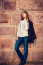 Beautiful young fashionable girl standing against the stone wall Royalty Free Stock Photos