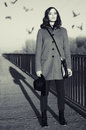 Beautiful young fashionable lady standing on bridge at sunrise while birds are flying over her head Royalty Free Stock Photos