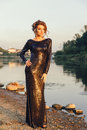 Beautiful young fashionable woman posing in dress at the river coast Royalty Free Stock Photo