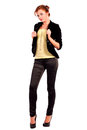 Beautiful young female fashion model dressed in black fitting trousers black jacket and yellow top on high heels standing Stock Image