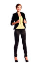 Beautiful young female fashion model dressed in black fitting trousers black jacket and yellow top on high heels standing Royalty Free Stock Photos
