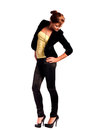 Beautiful young female fashion model dressed in black fitting trousers black jacket and yellow top on high heels standing and Stock Photos