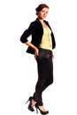 Beautiful young female fashion model dressed in black fitting trousers black jacket and yellow top on high heels standing Stock Photography