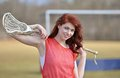 Beautiful young female lacrosse player caucasian in red jersey smiling while holding lax stick red hair Stock Image