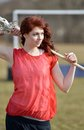 Beautiful young female lacrosse player caucasian in red jersey smiling while holding lax stick red hair looking off frame right Royalty Free Stock Photos