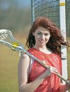 Beautiful young female lacrosse player red haired poses for a portrait with stick and ball next to net Stock Photography