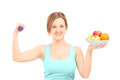 Beautiful young female posing with a dumbbell and fruits in a bo Royalty Free Stock Photos