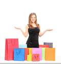 Beautiful young female posing with many shopping bags on a table isolated on white background Stock Photo