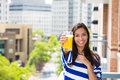 Beautiful young female relaxing on a balcony on a sunny summer day drinking orange juice portrait of in her new apartment Royalty Free Stock Photography