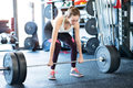 Beautiful young fit woman in gym lifting heavy barbell Royalty Free Stock Photo