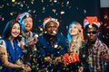 Friends at New Year`s party, wearing santa hats, dancing and blowing confetti Royalty Free Stock Photo