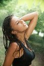 Beautiful young girl bathing under summer rain Stock Images