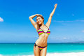 Beautiful young girl in bikini on a tropical beach. Blue sea in Royalty Free Stock Photo