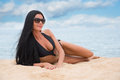 Beautiful young girl in a black bathing suit lying on the sand Royalty Free Stock Photos