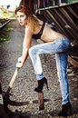Beautiful young girl in bra and jeans pulls railway lever Stock Image