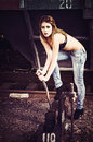 Beautiful young girl in bra and jeans pulls the railway lever Royalty Free Stock Photography