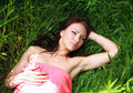 Beautiful young girl dreams lying on green grass the meadow in Stock Photo