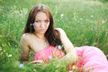 Beautiful young girl dreams lying on the meadow in green grass Stock Photography