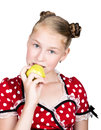 Beautiful young girl dressed in a red dress with white polka dots eating an apple. healthy food - strong teeth concept