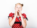 Beautiful young girl dressed in a red dress with white polka dots. Funny kids pamper and posing Royalty Free Stock Photo