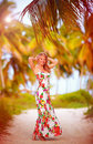 Beautiful young girl enjoys vacation in tropical palm grove the Royalty Free Stock Photos