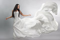 Beautiful young girl in flying white dress. Flowing fabric. Light white cloth flying Royalty Free Stock Photo