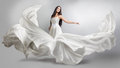 Beautiful young girl in flying white dress. Flowing fabric. Light white cloth flying