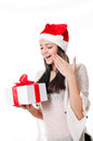Beautiful young girl with gift in hand on a white background santa hat Stock Image