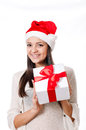 Beautiful young girl with gift in hand on a white background santa hat Stock Photos