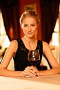 Beautiful young girl with glass of red wine alone in a restaurant Royalty Free Stock Photos