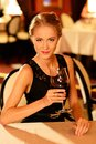 Beautiful young girl with glass of red wine alone in a restaurant Stock Photo