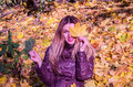 The beautiful young girl a happy woman smiling and holding a yellow maple leaves walking in autumn park Royalty Free Stock Photo