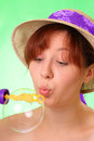Beautiful young girl in a hat blowing soap bubbles Stock Photos