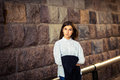 Beautiful young girl hipster standing against the stone wall Royalty Free Stock Photo