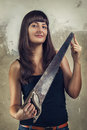 Beautiful young girl holding saw over grunge Royalty Free Stock Photography