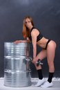 Beautiful young girl with an ideal figure and dumbbell in hand leans the elbows on barrel Royalty Free Stock Photo