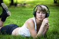 Beautiful young girl listening to music on her headphones as she relaxes in the garden or park lying on her stomach on the green Stock Photography