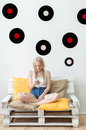 Beautiful young girl listening to music at home sitting on the c couch Stock Photos