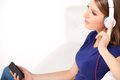 Beautiful young girl listens to music on headphones. Royalty Free Stock Photo