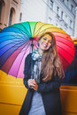 Beautiful young girl with long hair standing under a bright colored umbrella and smiling Royalty Free Stock Photo