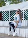 The beautiful young girl with long hair in sunglasses sits at white wooden steps summer Stock Image