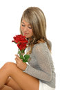 Beautiful young girl looking at red rose with long hair on white background shot in studio over white Stock Photos