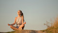 Beautiful young girl meditating on the hill in the rays of the setting sun Royalty Free Stock Photo