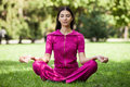 Beautiful young girl meditating in a park Stock Photography