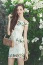 Beautiful young girl model posing near blooming lilacs at spring Royalty Free Stock Photo