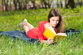 Beautiful young girl reads book in park at summer Royalty Free Stock Photos